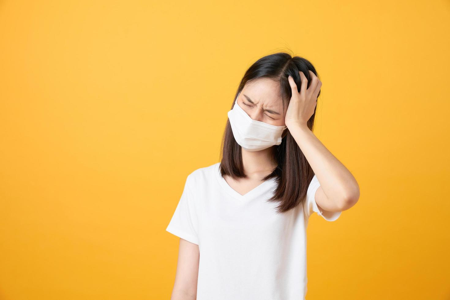 Woman wearing mask while holding head photo