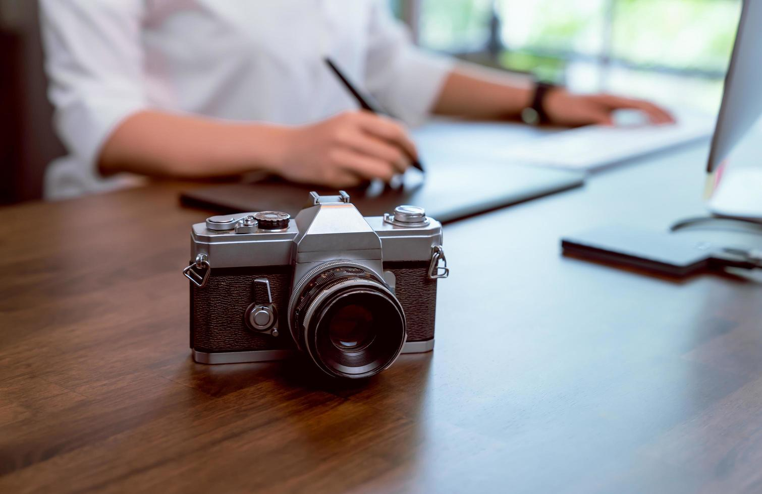 Film camera on desk with woman editing photos