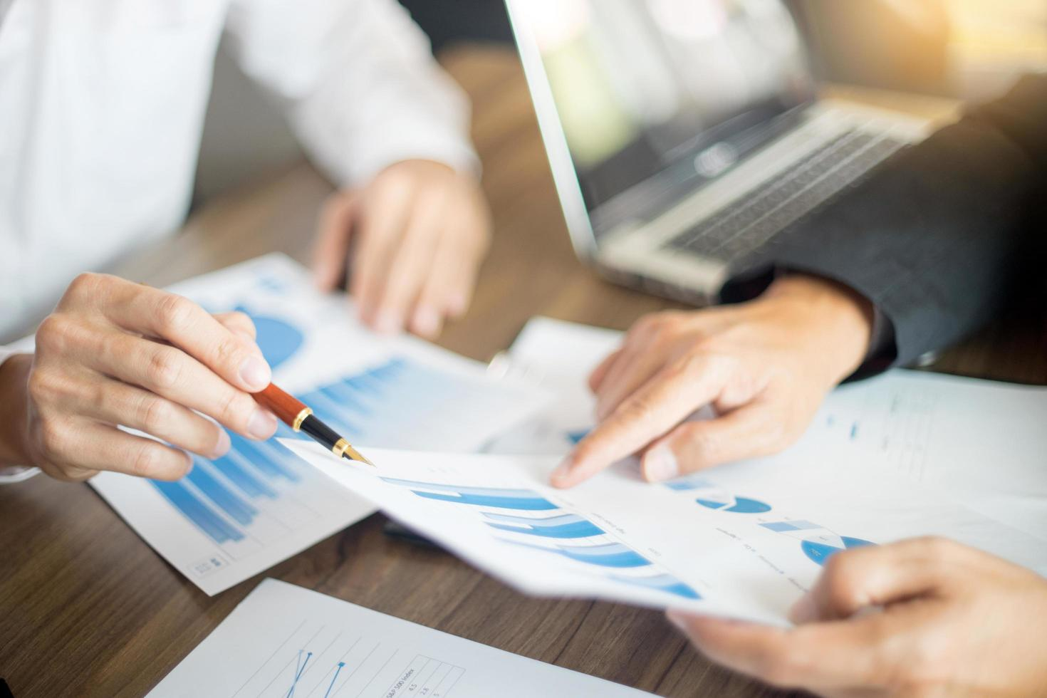 Business professionals pointing to charts photo