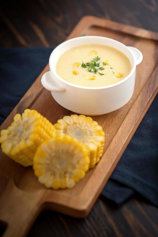 Corn chowder with side corn on wooden dish photo