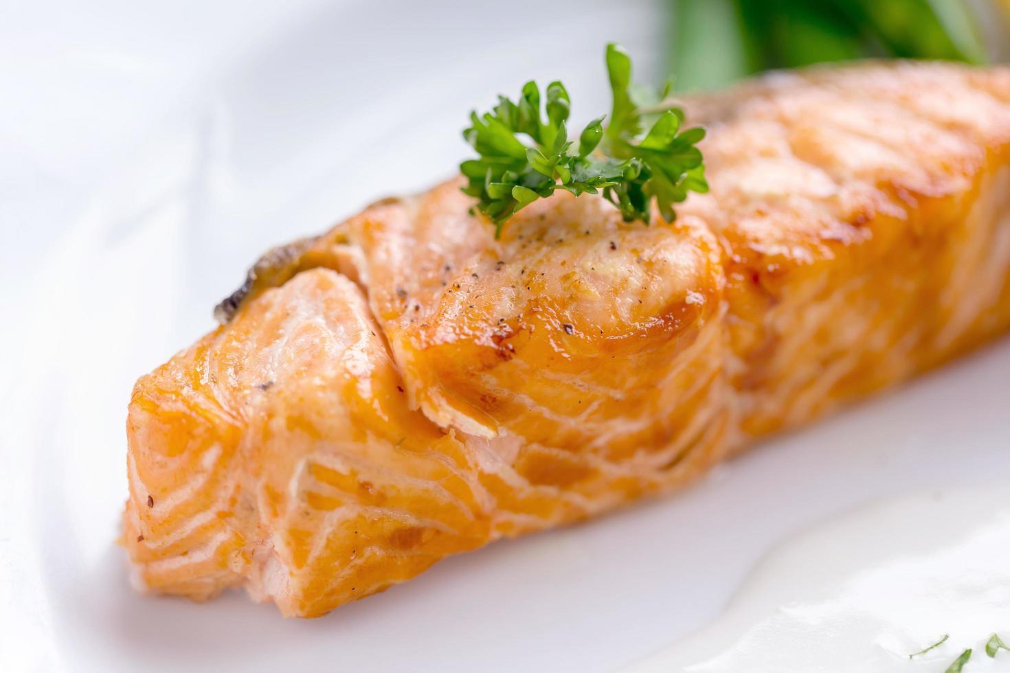 Salmon steak with white sauce on a white plate photo