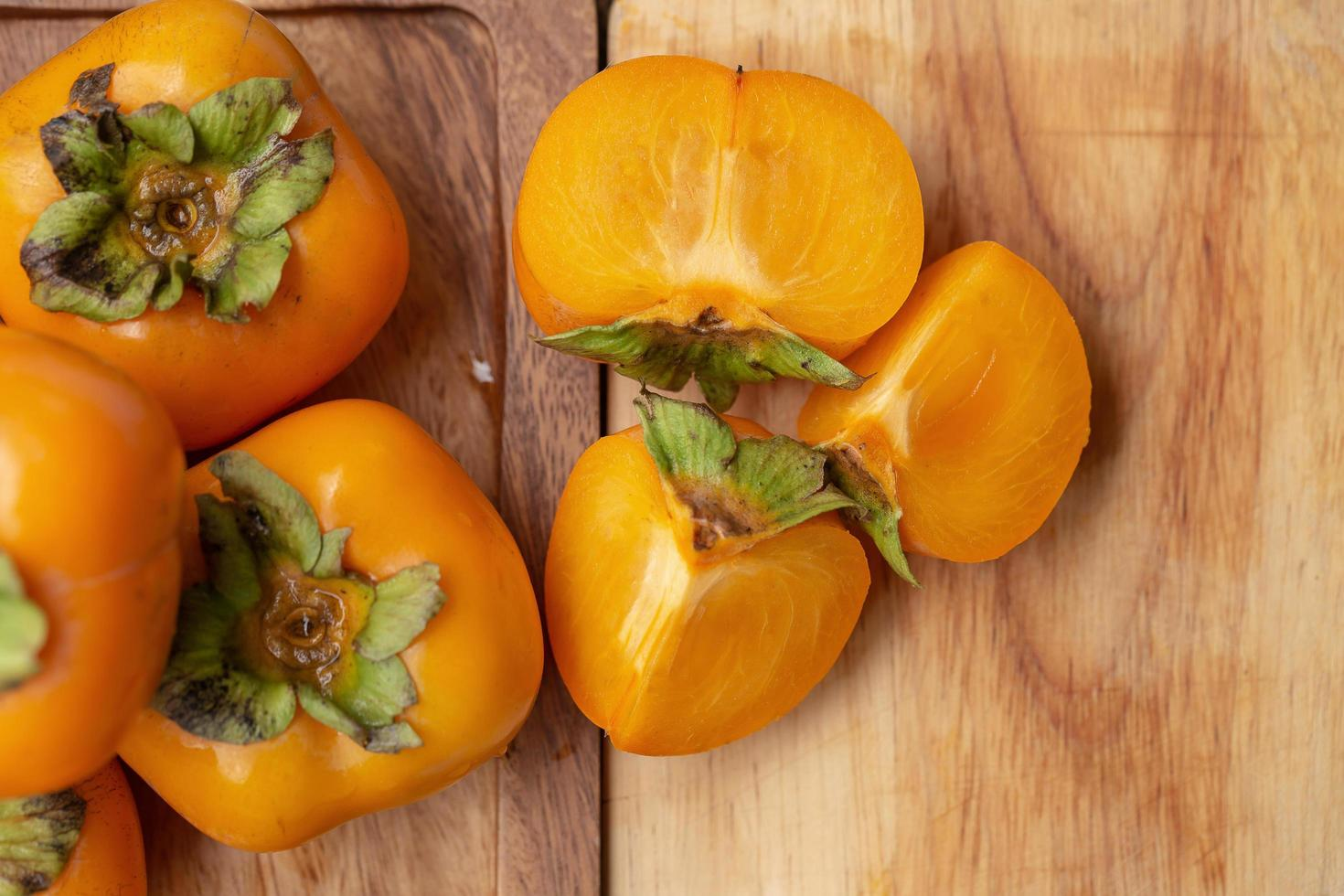 Fresh ripe persimmons on wooden table photo