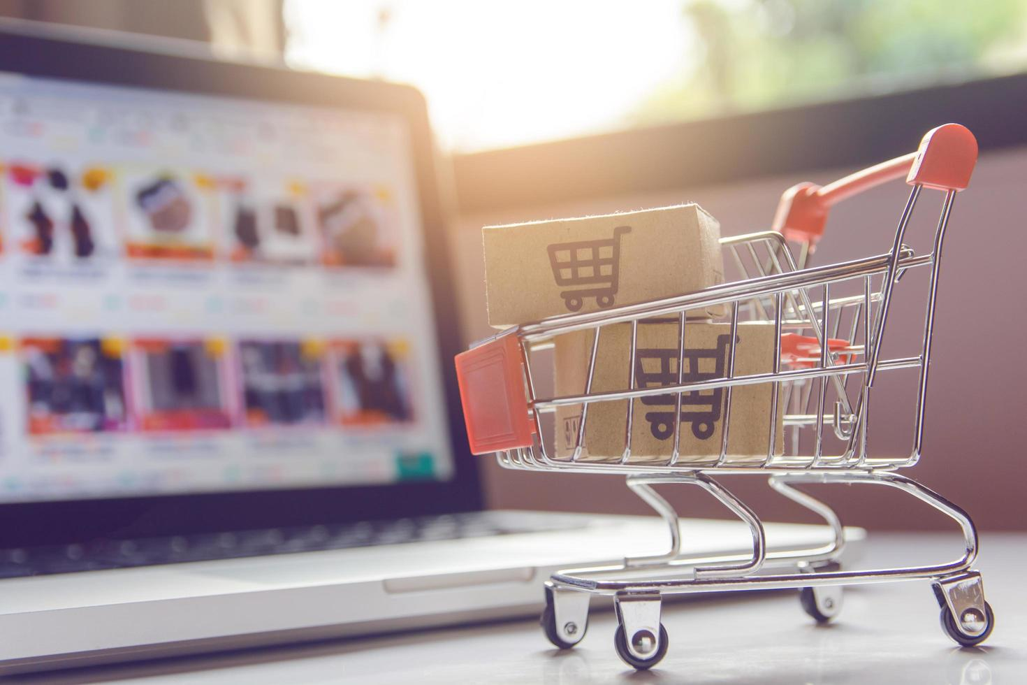Miniature shopping cart in front of laptop photo