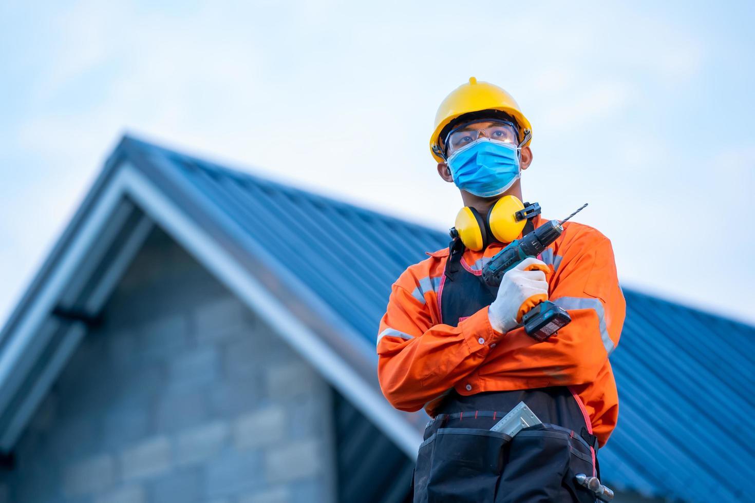 trabajador de la construcción posando con taladro eléctrico foto