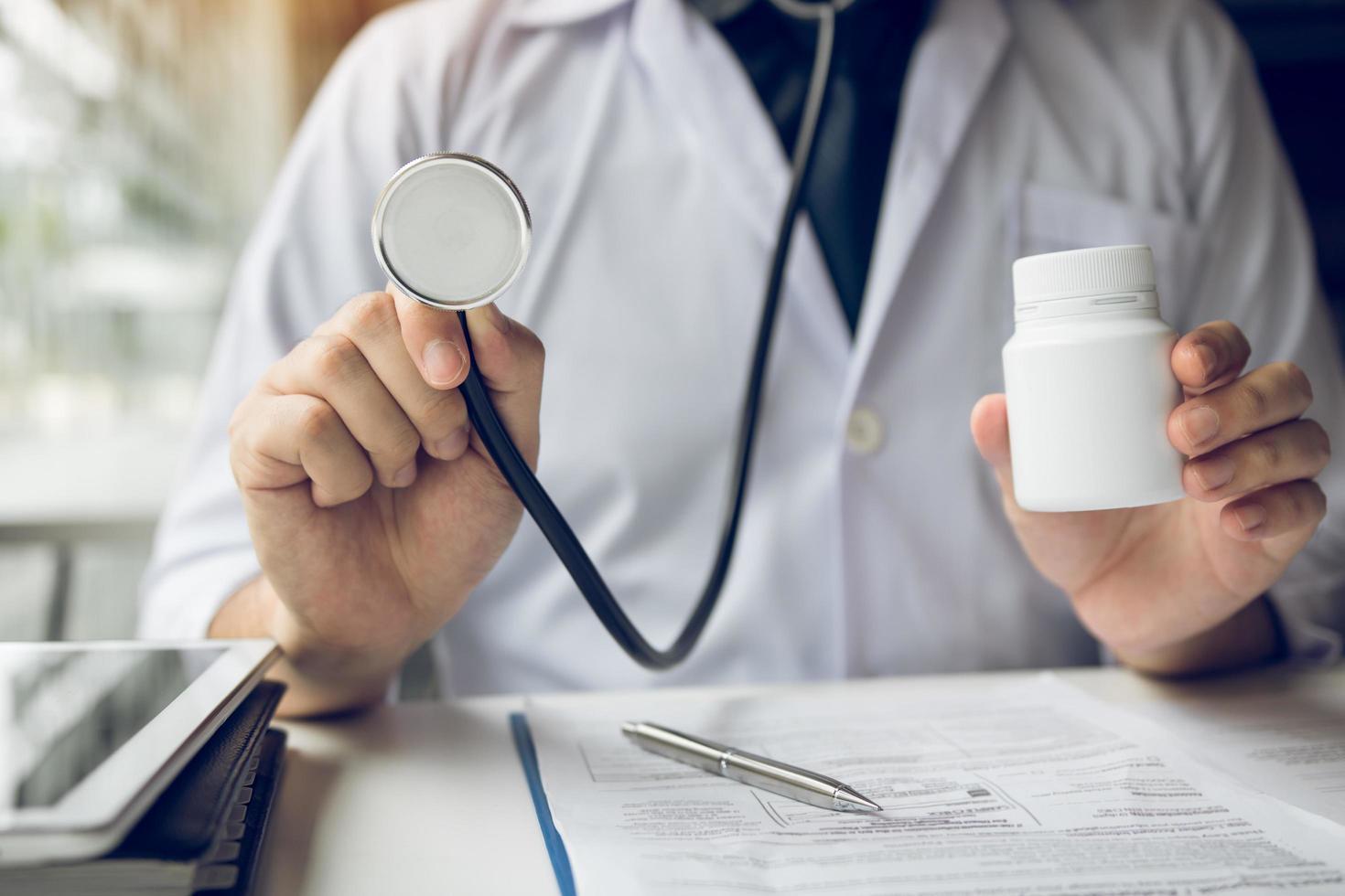 Doctor holding stethoscope and medicine bottle photo