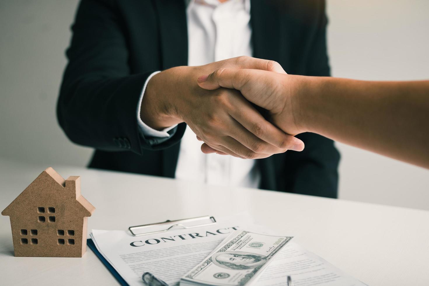 agente inmobiliario y cliente estrechándole la mano foto