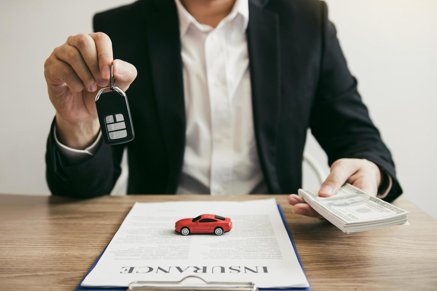 Car salesman handing keys and money to client photo