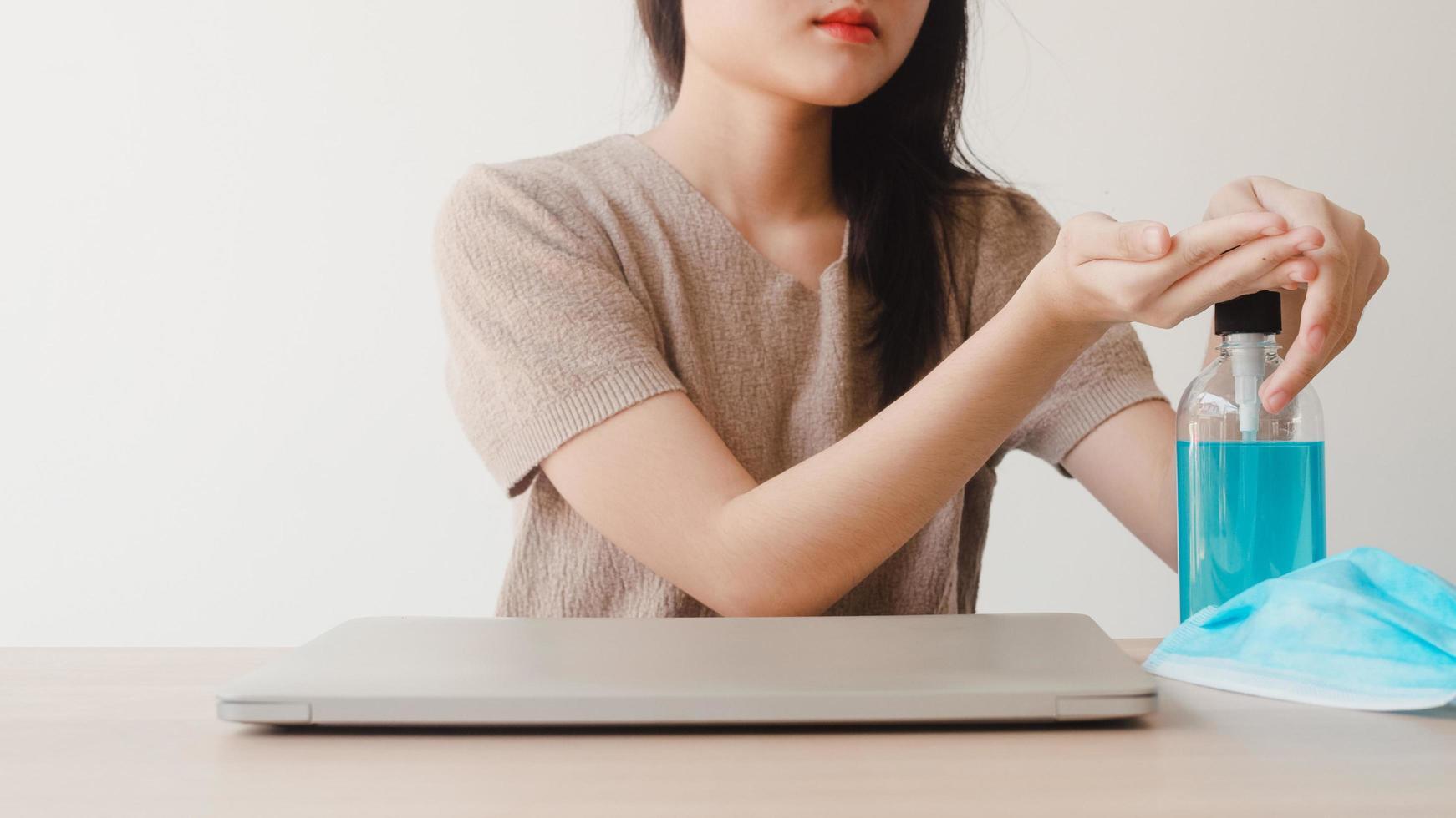 mulher asiática usando álcool gel desinfetante para as mãos em casa foto
