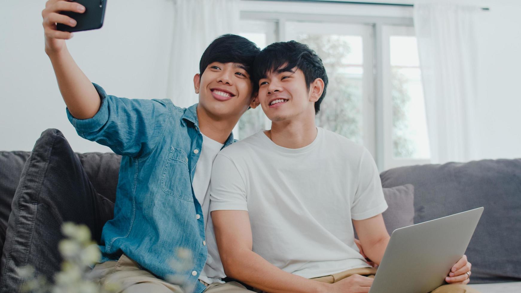 joven pareja gay se toma una selfie en casa. foto
