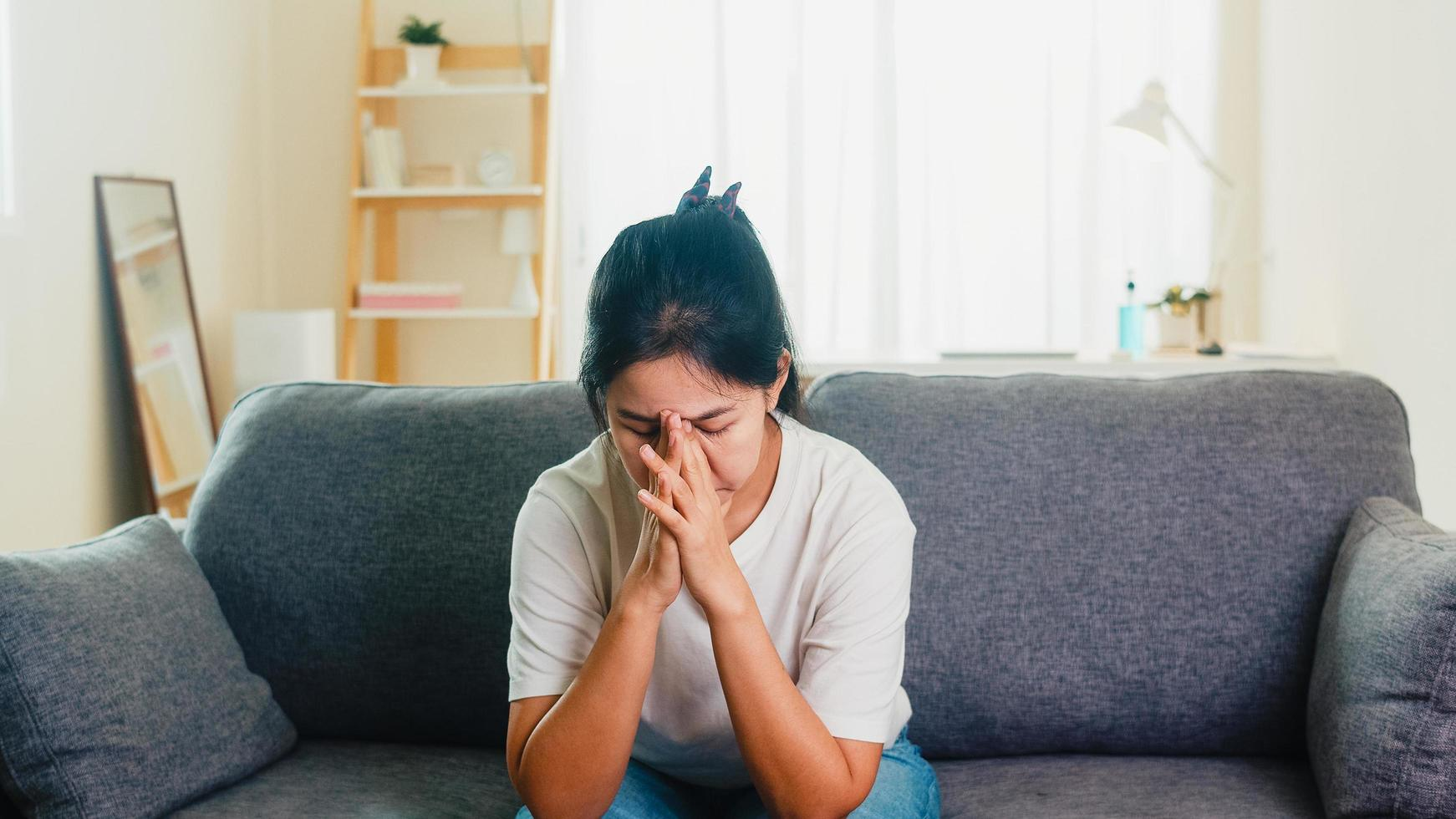 Asian businesswoman stressed with headache sitting on sofa in living room photo