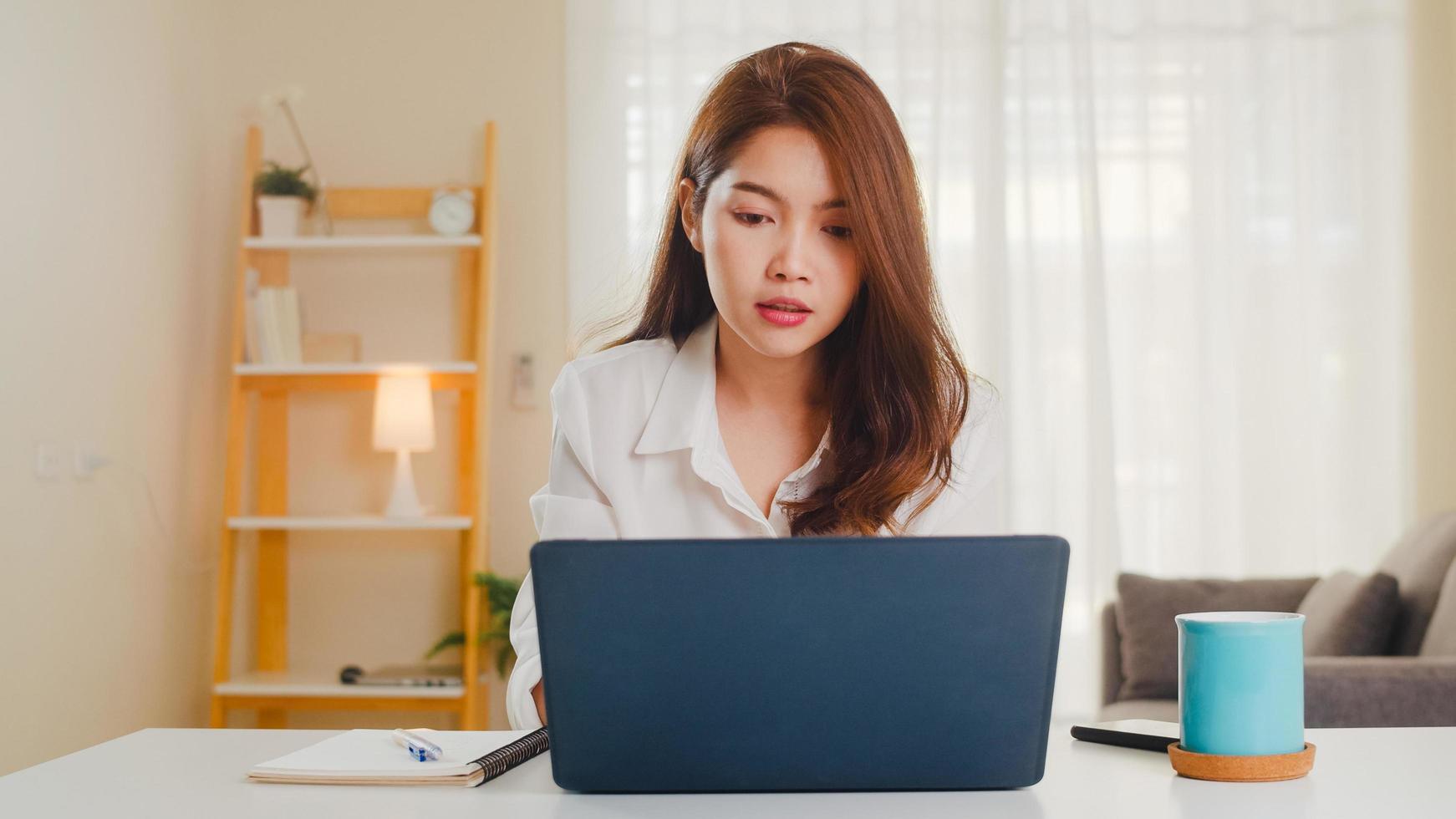 empresária asiática usando laptop conversar com colegas. foto
