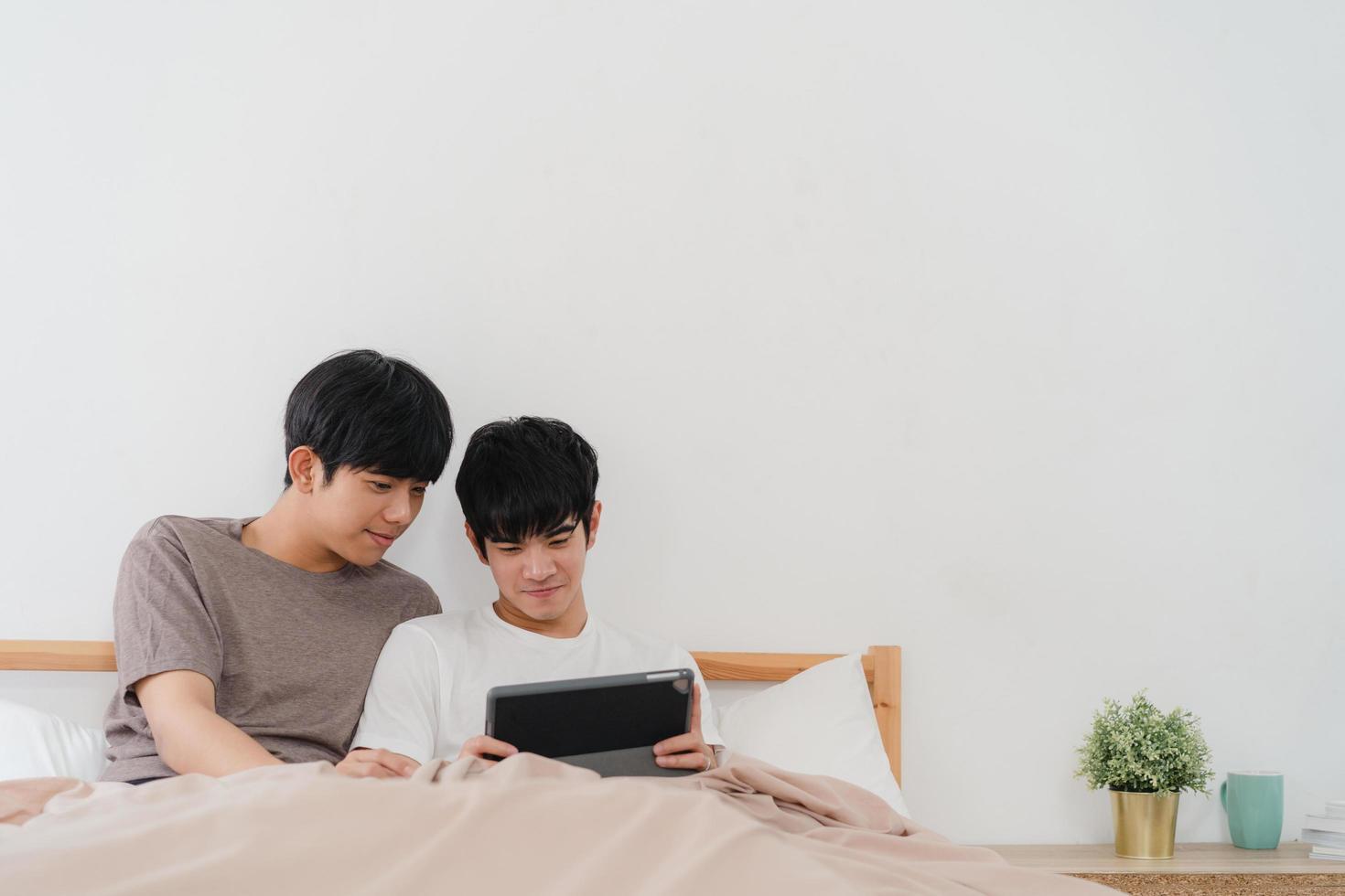 joven pareja gay asiática usando tableta en casa foto