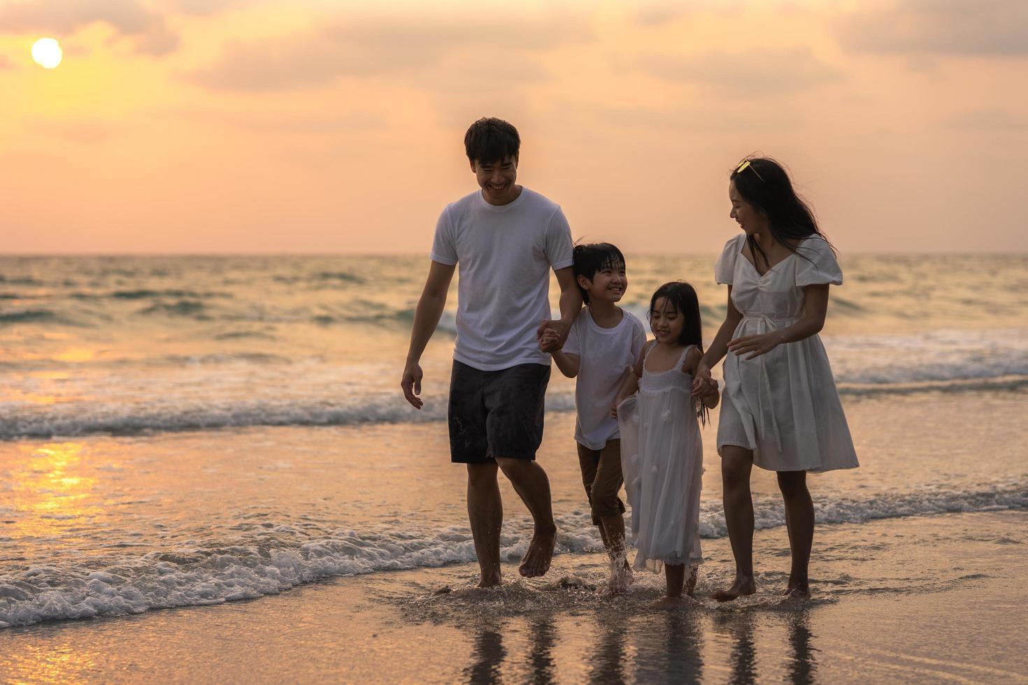 familia asiática disfruta de vacaciones en la playa foto