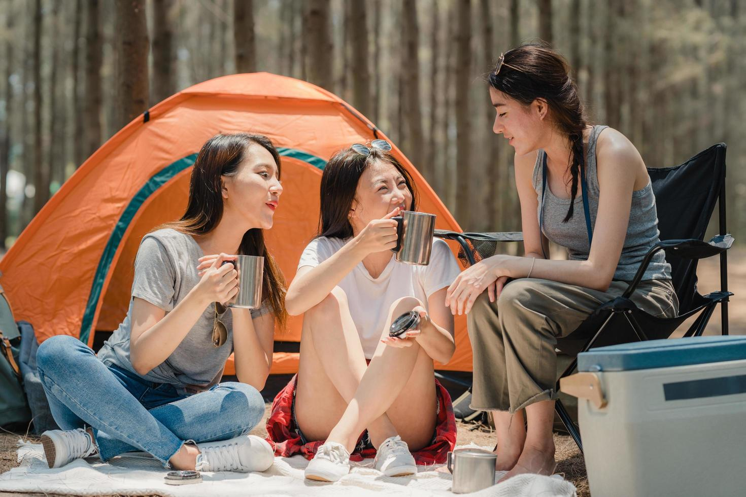 Group of young Asian friends camping together in a forest. photo