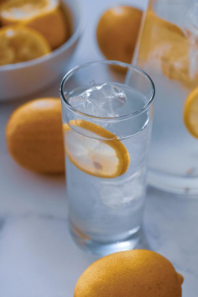 hohes Glas Wasser zwischen frischen Zitronen foto