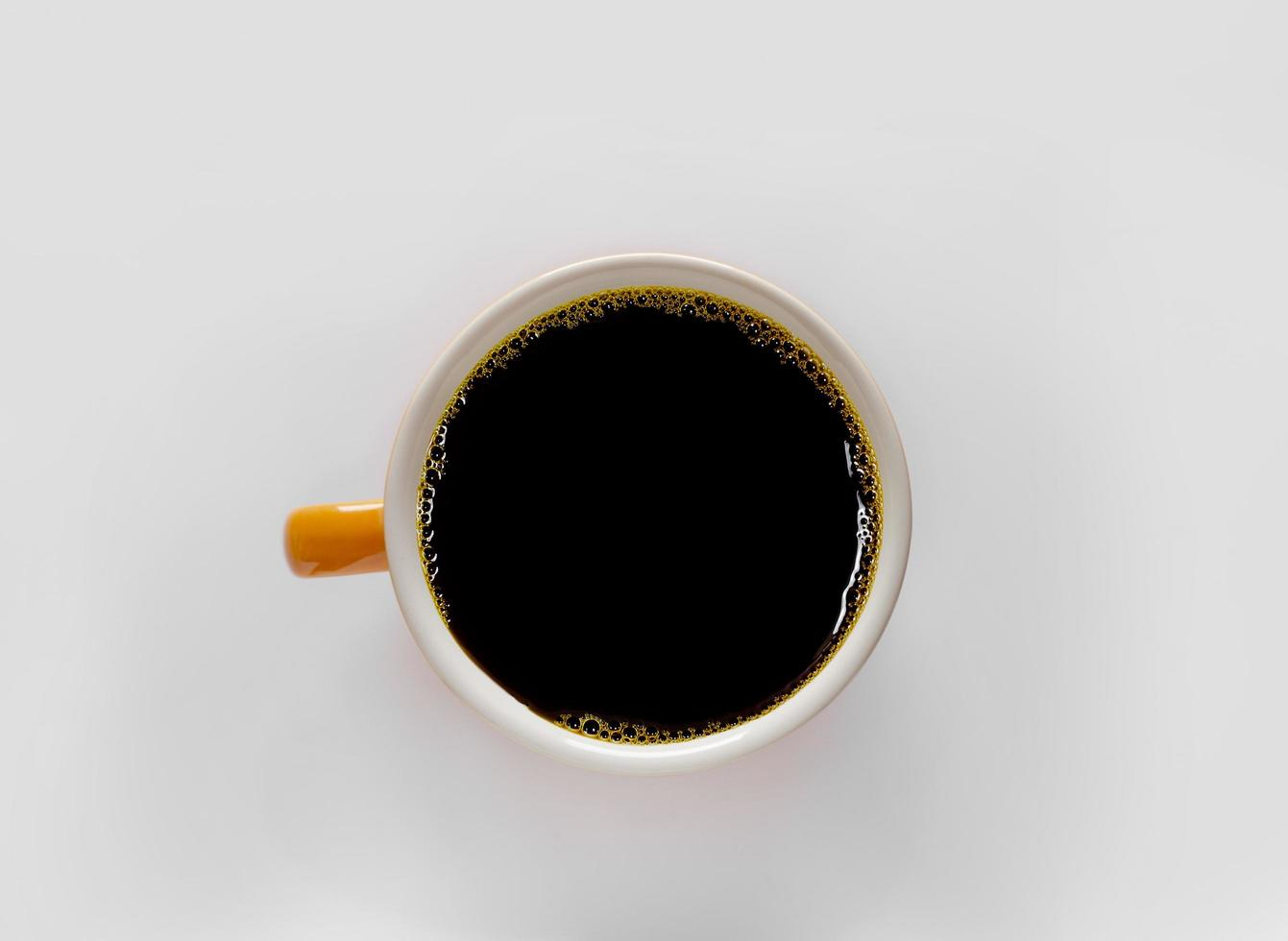 Flat lay view of black coffee in a bright orange cup photo