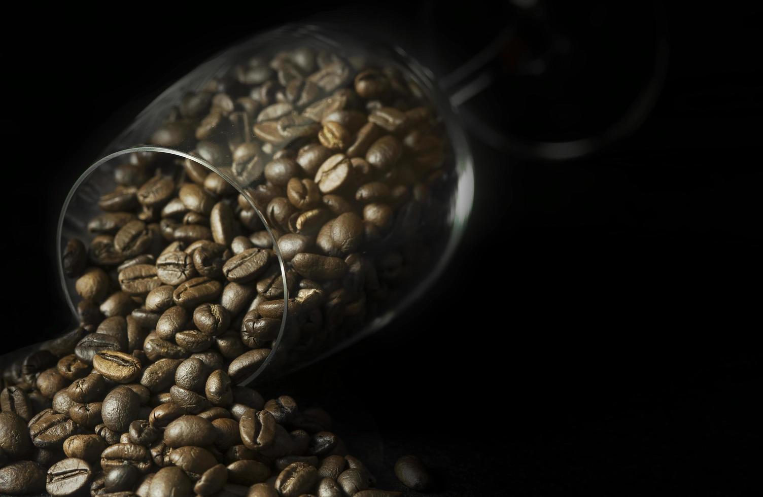 granos de café en copa de vino sobre fondo negro foto