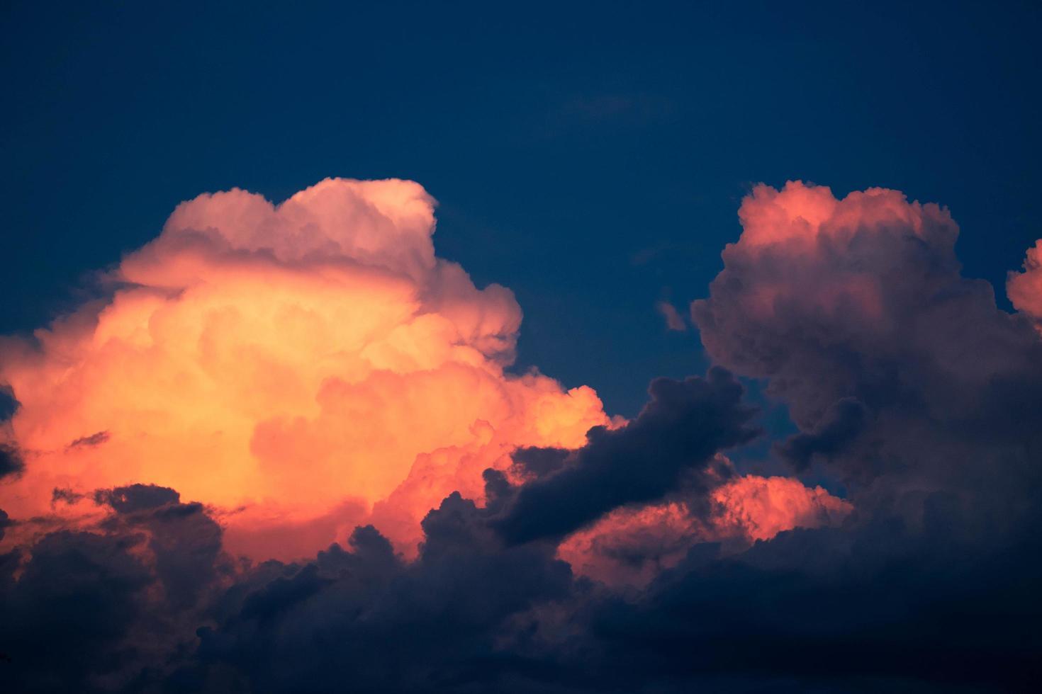 nuvens vermelhas em um céu azul escuro foto