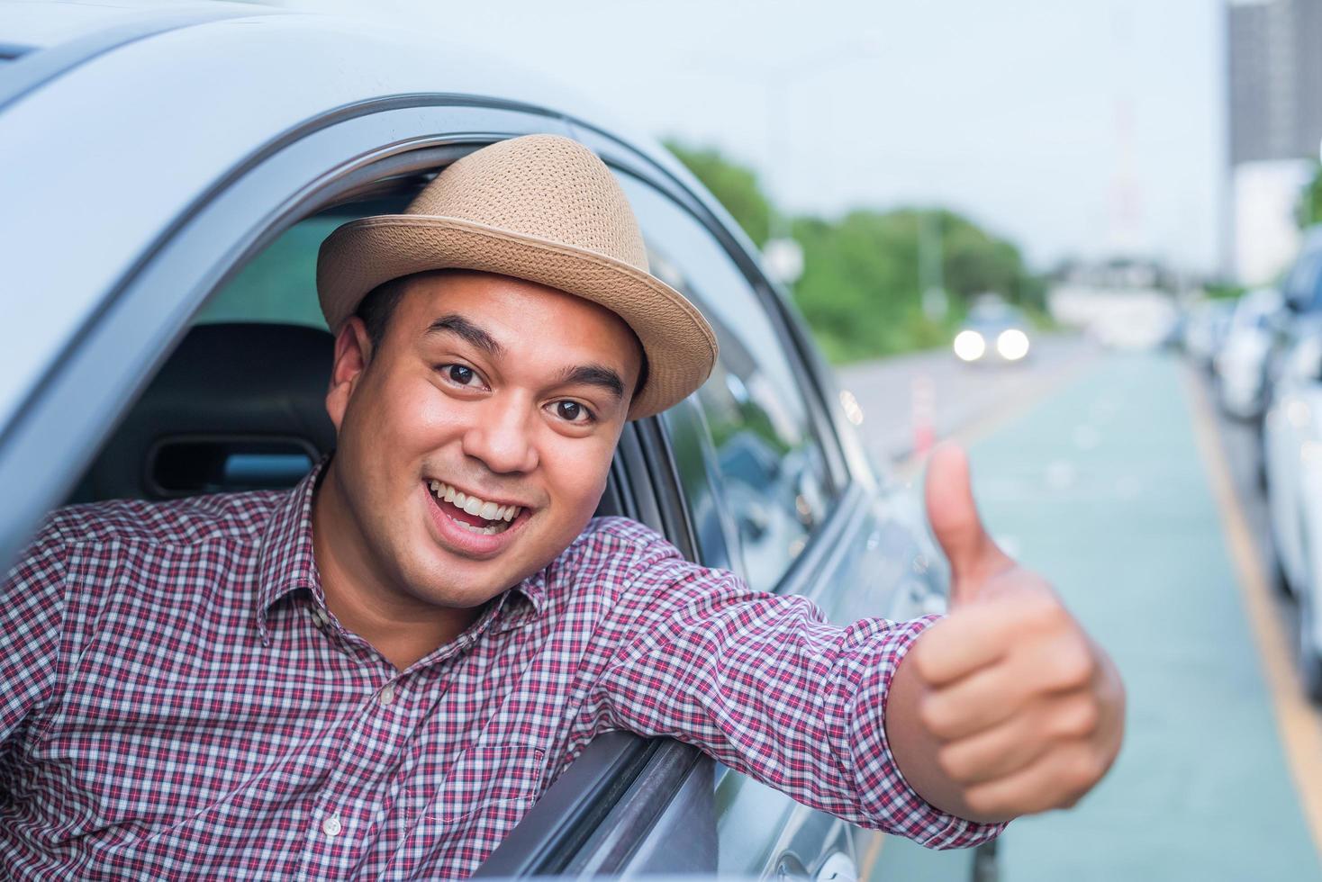 homem dando polegares para fora da janela do carro foto