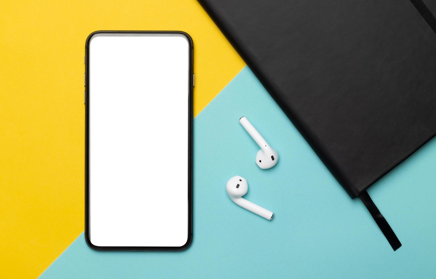 Smartphone and earbuds on yellow and blue background photo