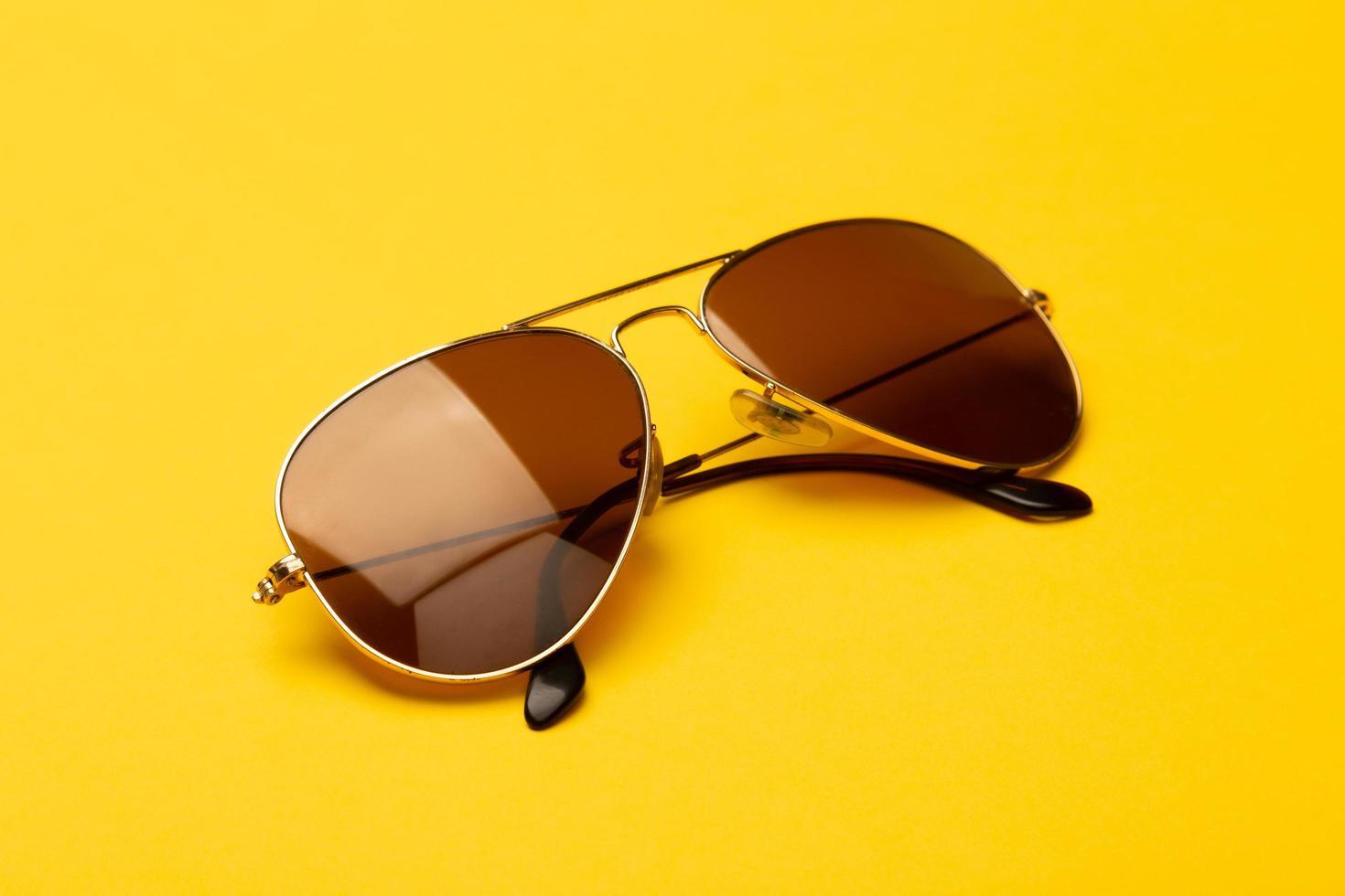 óculos de sol aviador em fundo amarelo foto