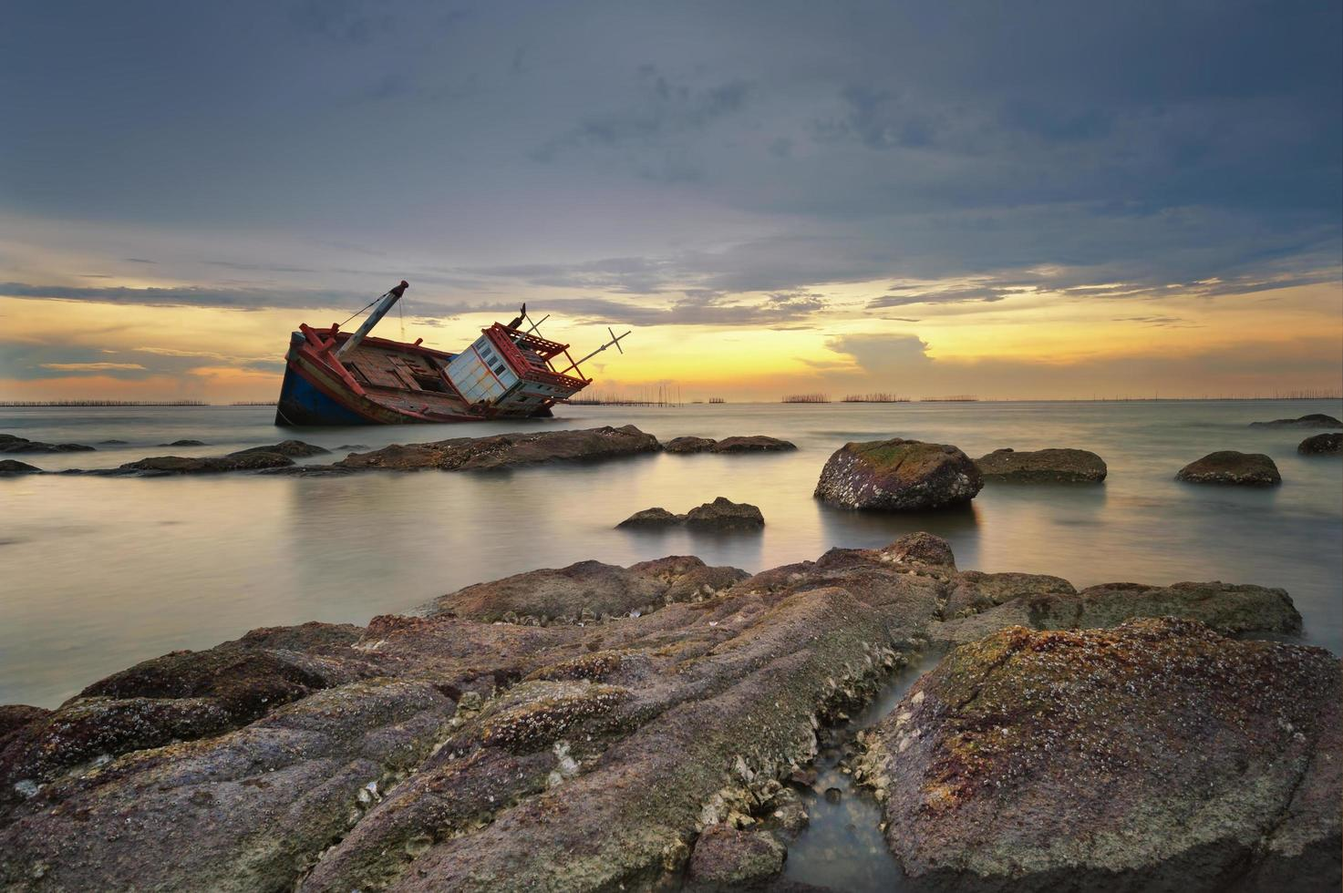 Shipwrecked boat at sunset photo