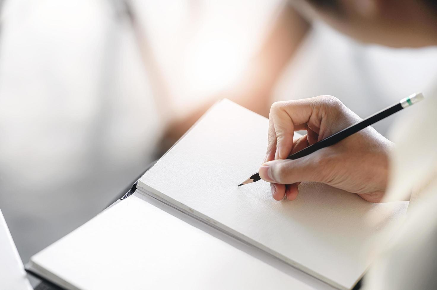 Man hand writes on notebook with pencil photo