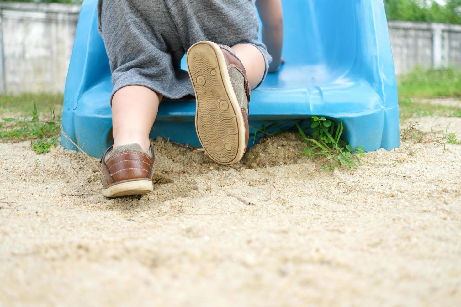 Little kid climbing up playground slide photo