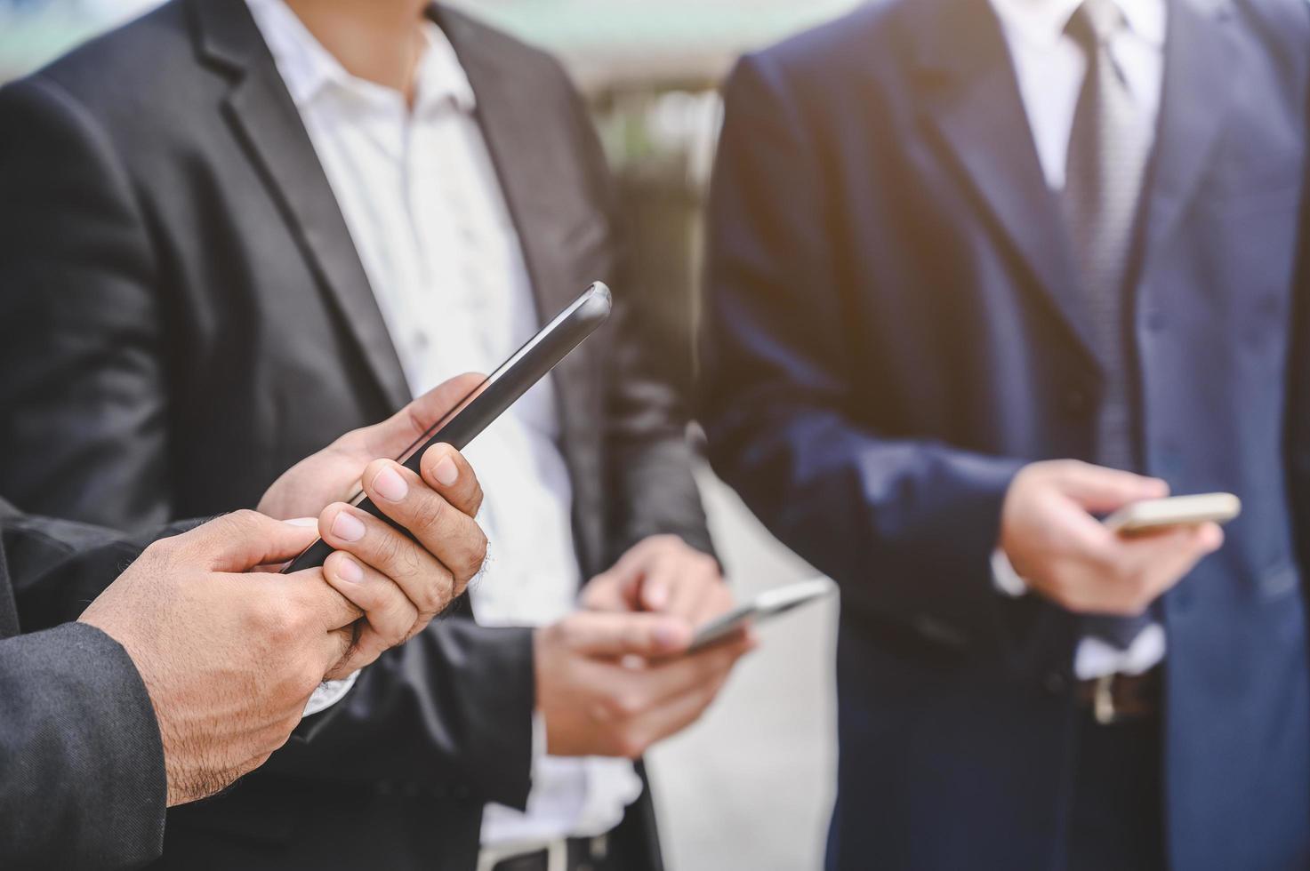 Group of businessmen using smartphones photo