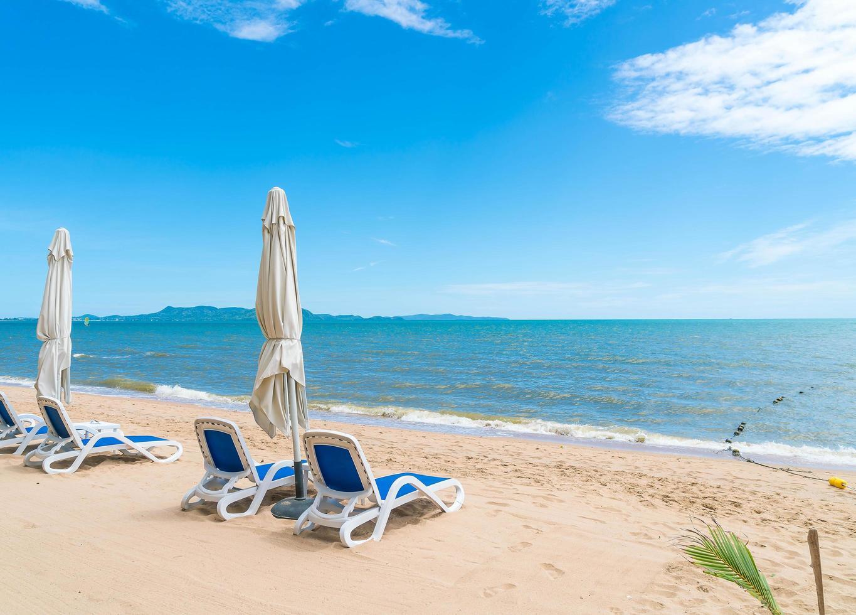 Beach chairs line a tropical shoreline  photo