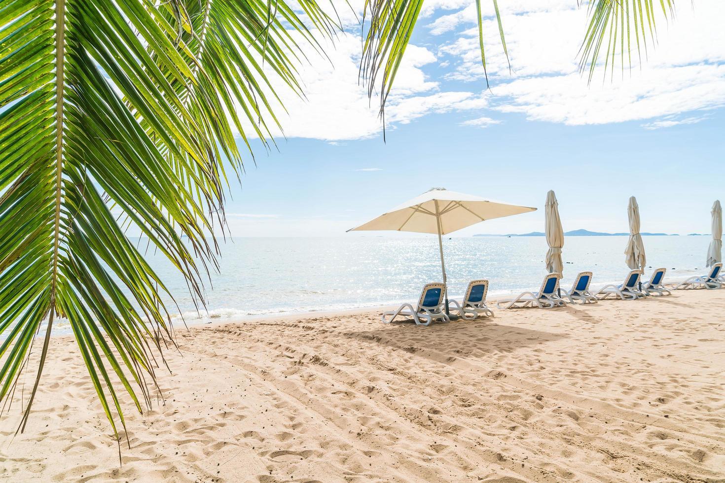 Tropical beach scene with open umbrella photo