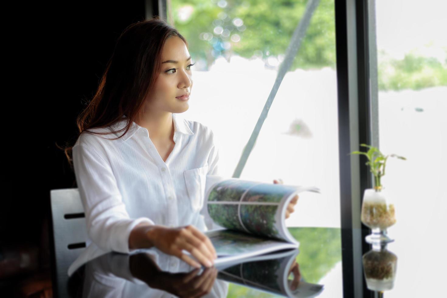 Mujeres asiáticas sonriendo y leyendo un libro en el café foto