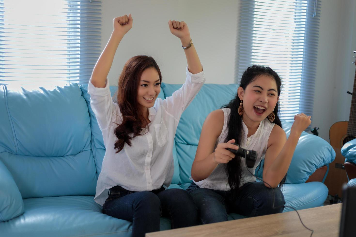 Asian  women playing video games  at home photo