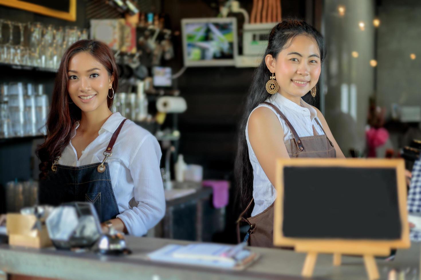 Baristas asiáticos femeninos sonriendo detrás del mostrador de la cafetería foto