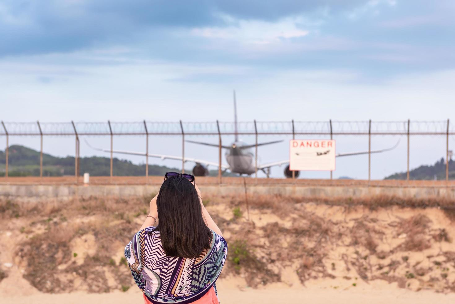 mujer fotografiando avión foto