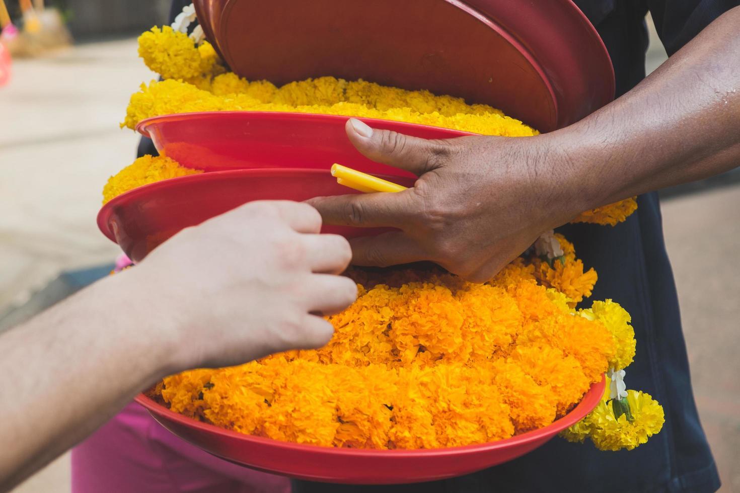 Seller's hand picking a tray of fresh marigold garland photo