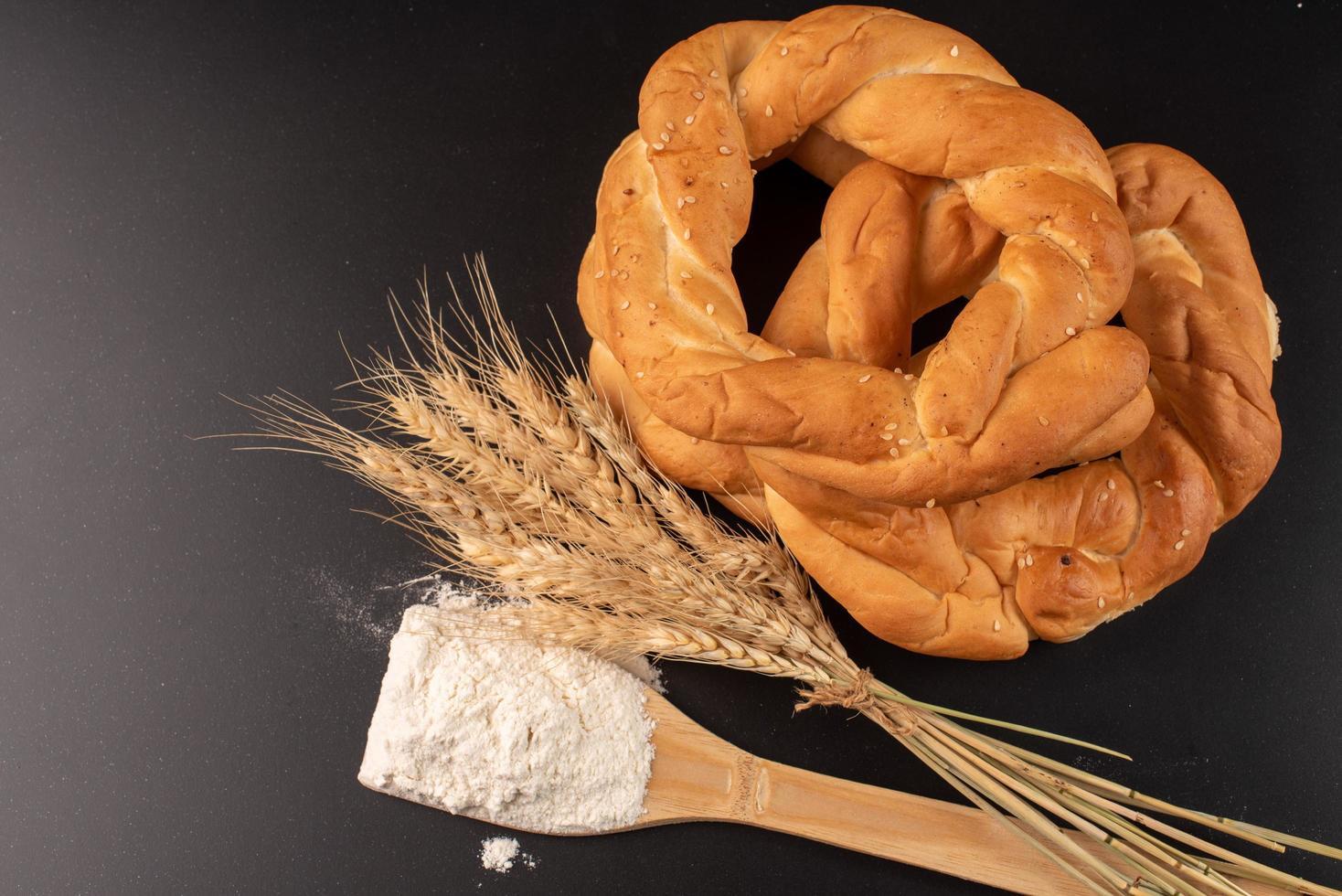 Pretzels and wheat on dark background photo