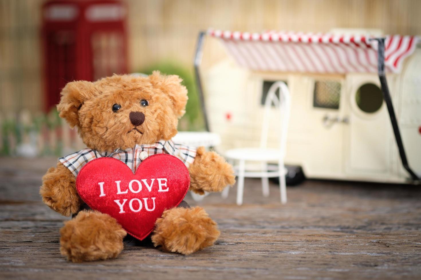 Teddy bear holding heart-shape pillow photo