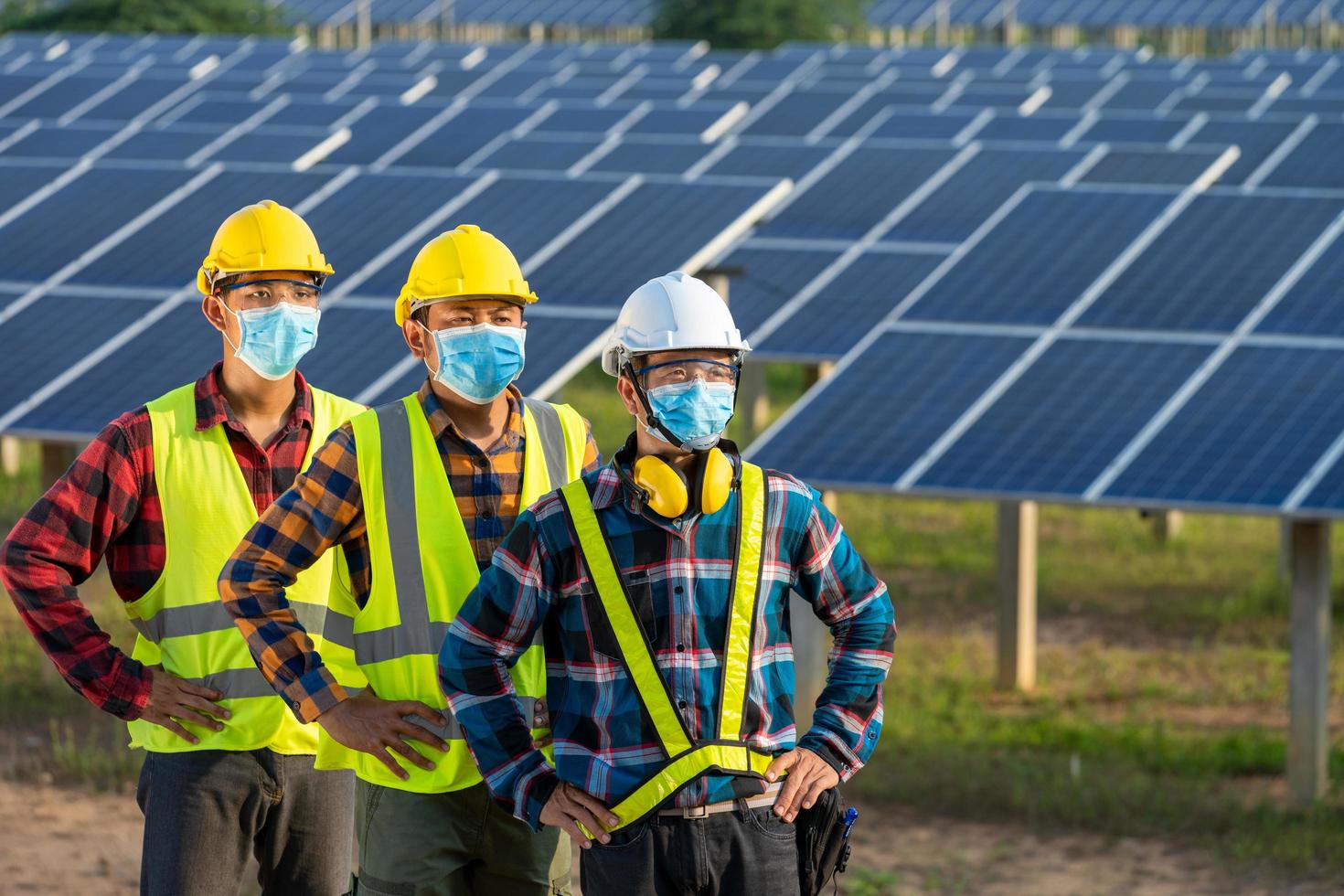 Masked workers next to solar panels photo