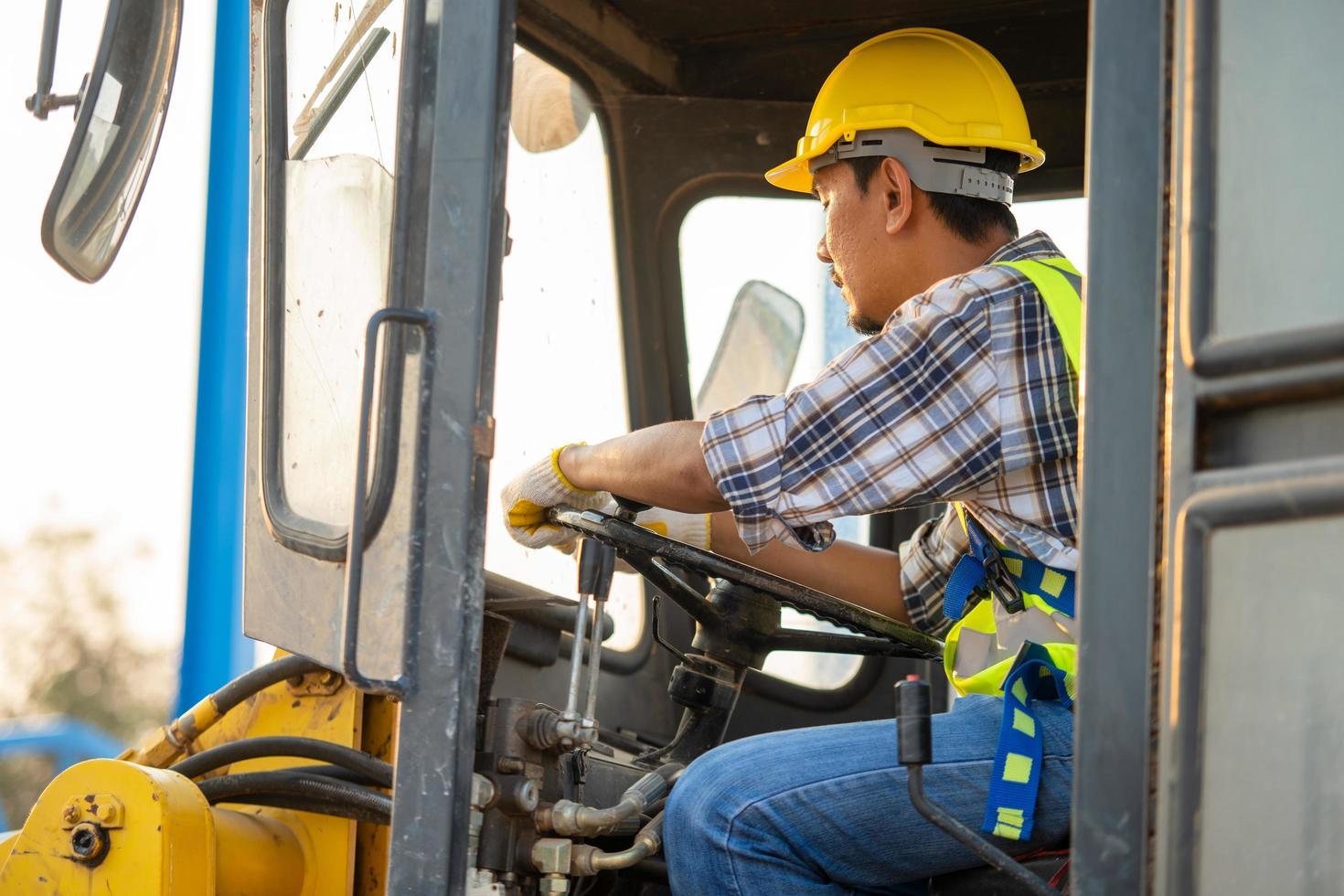 Construction worker driving backhoe loader photo