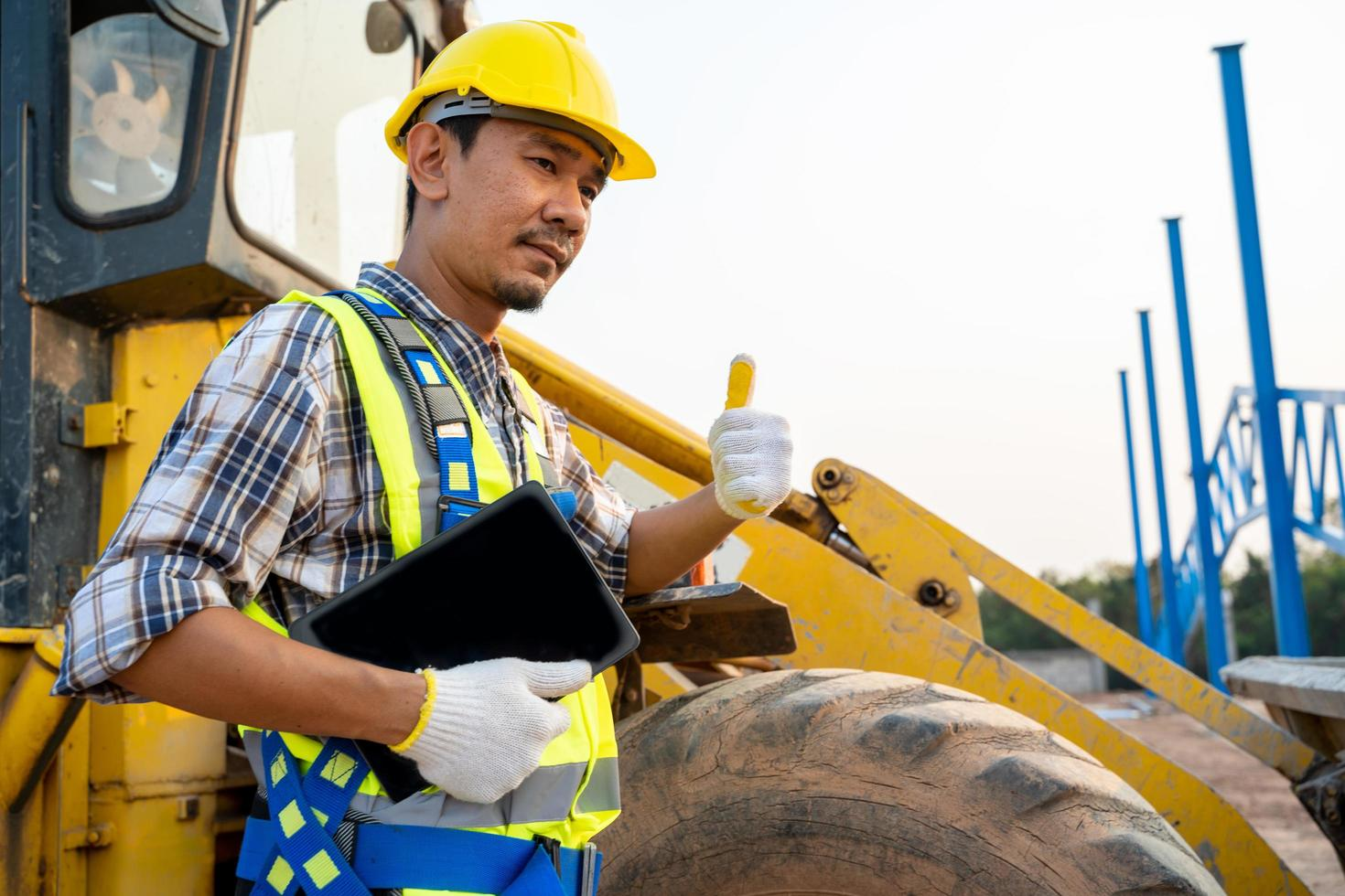 Trabajador de la construcción junto a la retroexcavadora foto