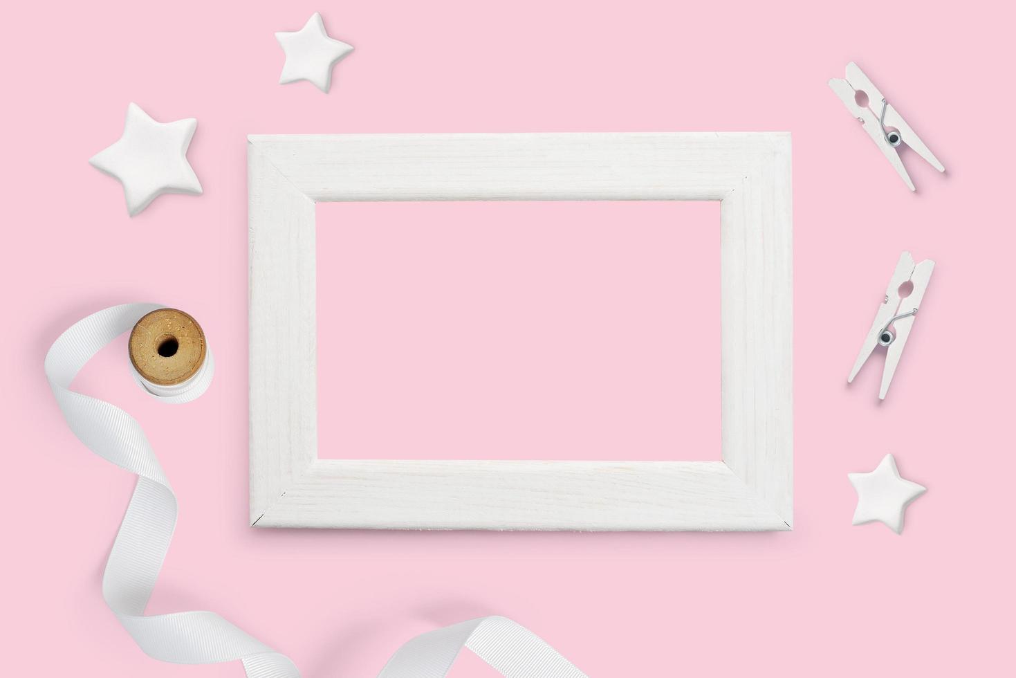 maqueta de marco de madera blanca, estrellas blancas, cinta y pinzas para la ropa foto