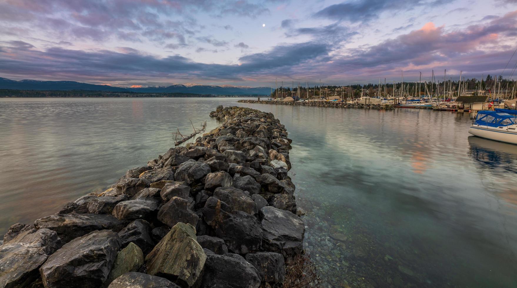 Gray rocks near body of water under blue sky photo