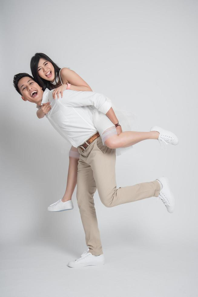 Happy groom gives a bride piggyback ride photo