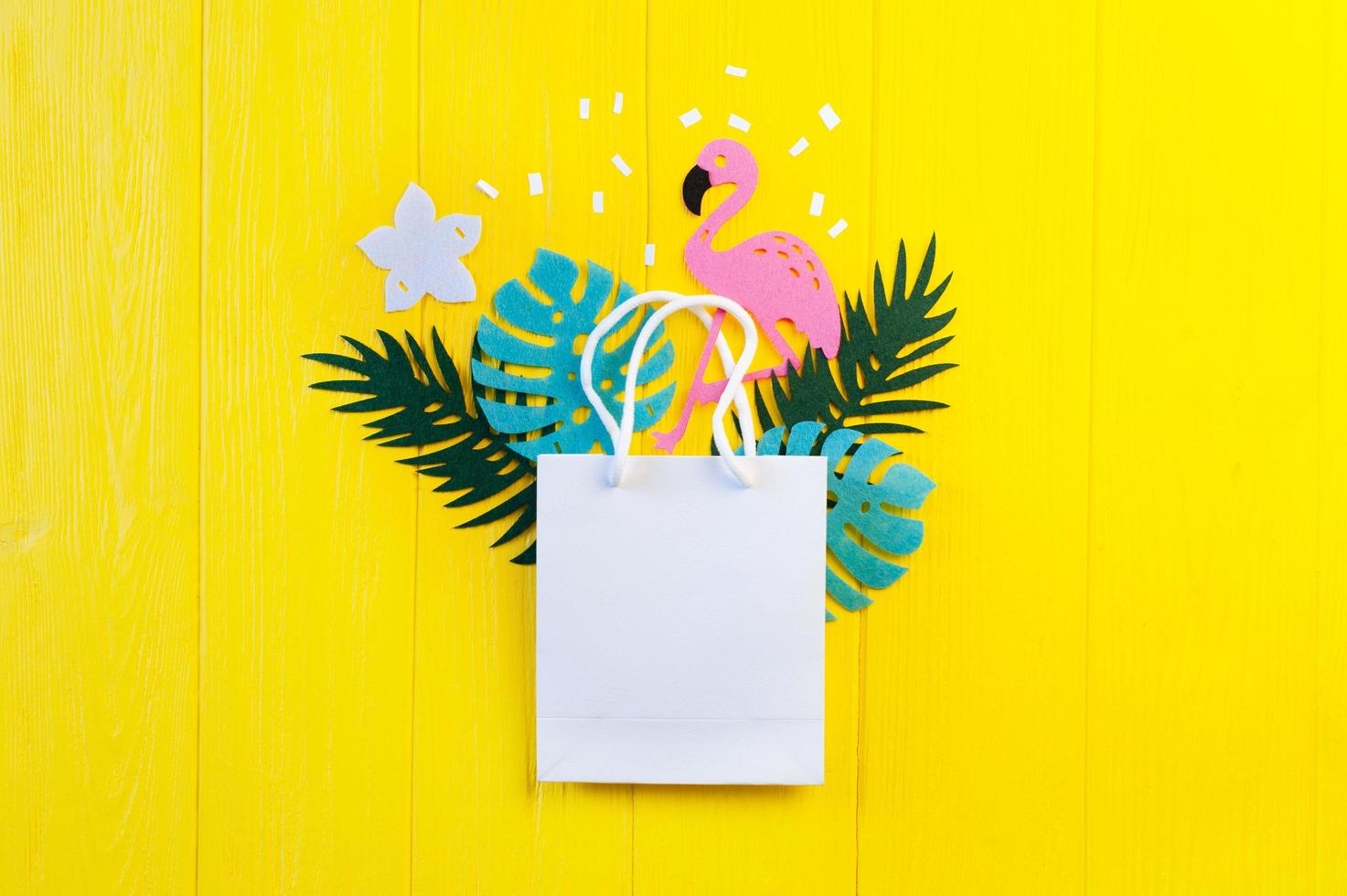 Mockup of blank paper with leaves and flamingo on yellow wooden background photo