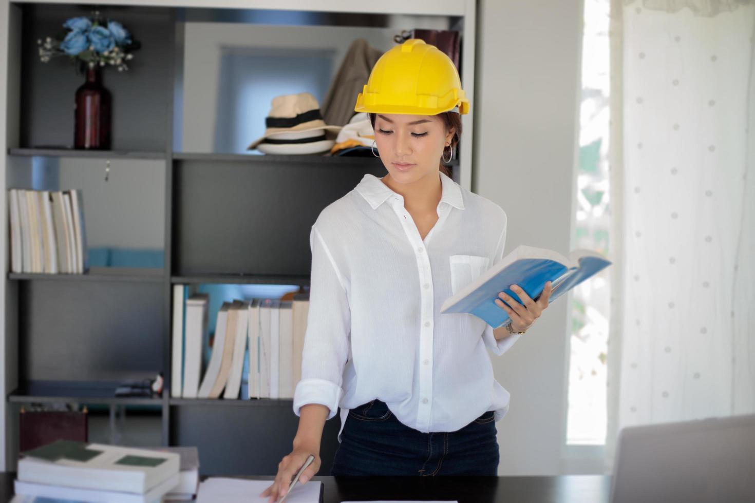 mujer asiática con casco en la oficina foto
