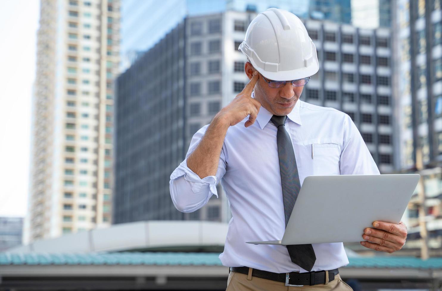 Businessman in hard hat with laptop photo