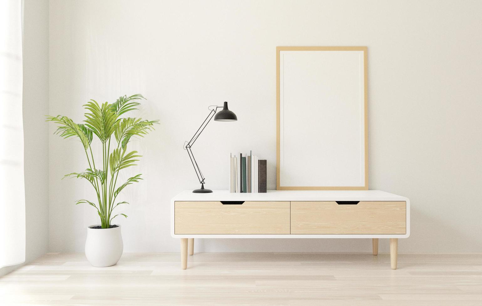 Dresser table with white poster frame, books, lamp, and plant photo