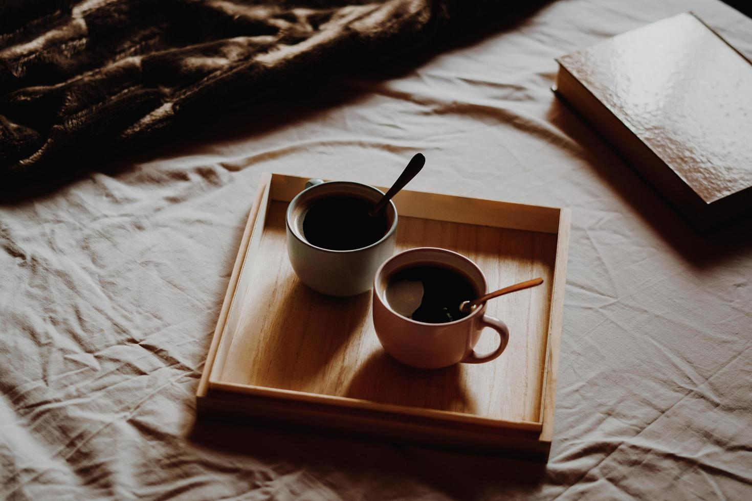 Cups of coffee on wooden tray on bed photo