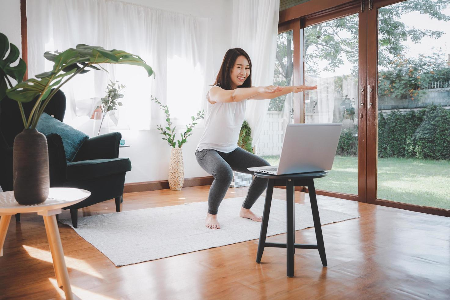 Woman learning online workout excercise class at home from laptop photo
